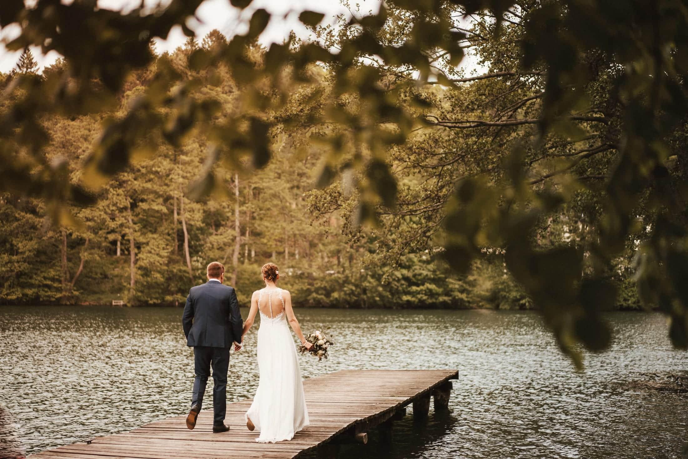 Das Brautpaar genießt gemeinsam einen ruhigen Moment. Sie gehen den Steg herab, während Ihre Gäste von einem Entertainer unterhalten werden.