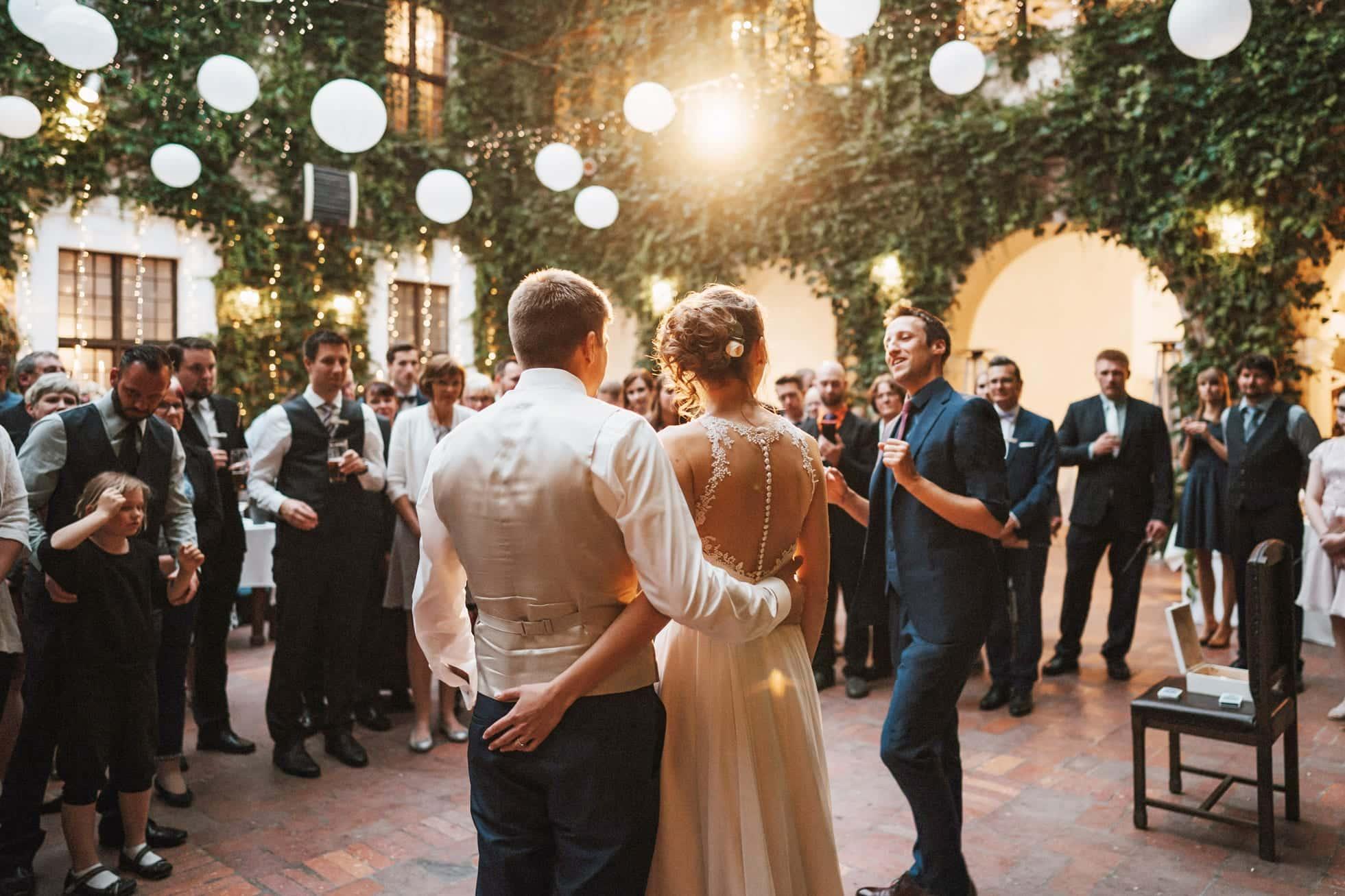 Das Brautpaar steht Arm in Arm mit dem Rücken zum Fotografen. Man sieht in das Gesicht des Zauberers auf ihrer Hochzeit und in die Gesichter ihrer Gäste. Die stehen im Halbkreis um die beiden herum und hören dem Zauberer gespannt zu.