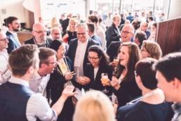 Die Gäste lachen ausgelassen über die Magie von Fabian Schneekind zum 50. Geburtstag eines deutschen Technologie Konzerns.