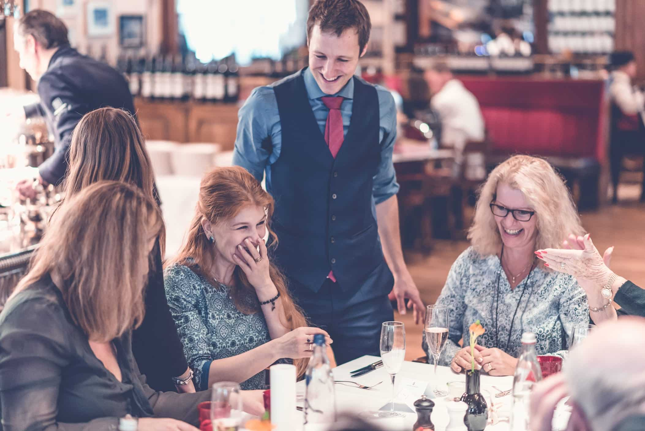 Die Gäste auf einer Feier sitzen am Tisch und lachen und staunen zusammen über die Illusionen des Magiers.
