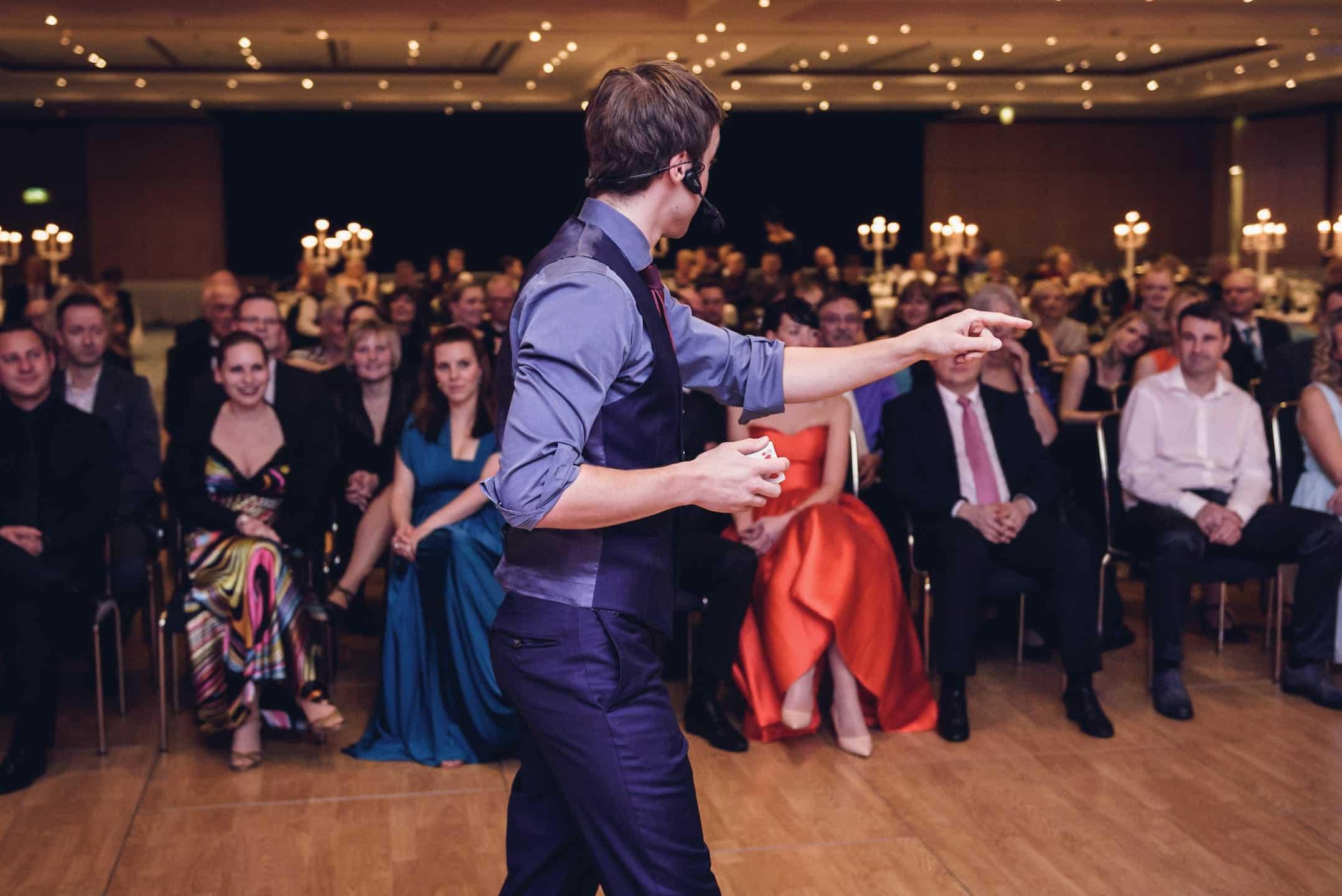 Bei einer Ballnacht haben sich alle Gäste herausgeputzt und sehen sich die Bühnenshow vom Zauberer an. Dieser zeigt mit seiner Hand an den Ort, wo etwas Unglaubliches passieren wird. In der anderen Hand hält er Spielkarten.