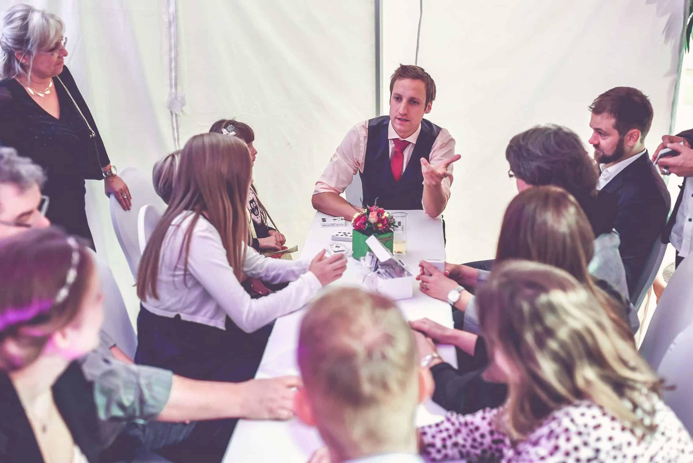 Bei einer Teambuilding Veranstaltung lernen Die MItarbeiter einen Zaubertrick mit Spielkarten vom Zauberer.