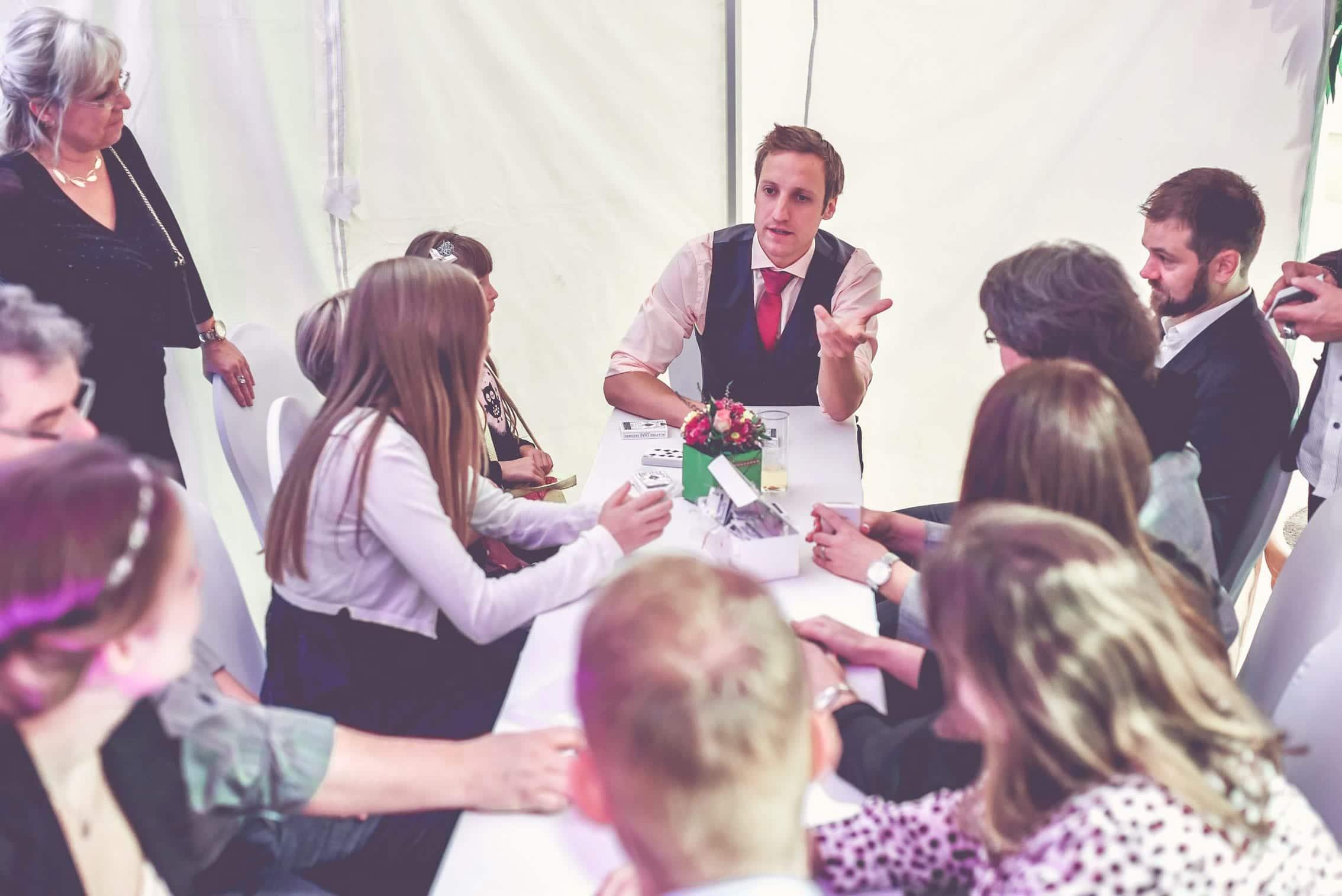 Der Zauberer bringt den Mitarbeitern bei einer Betriebsfeier einen Zaubertrick bei. Sie sitzen am Tisch und hören aufmerksam zu. Auf dem Tisch liegen Spielkarten.