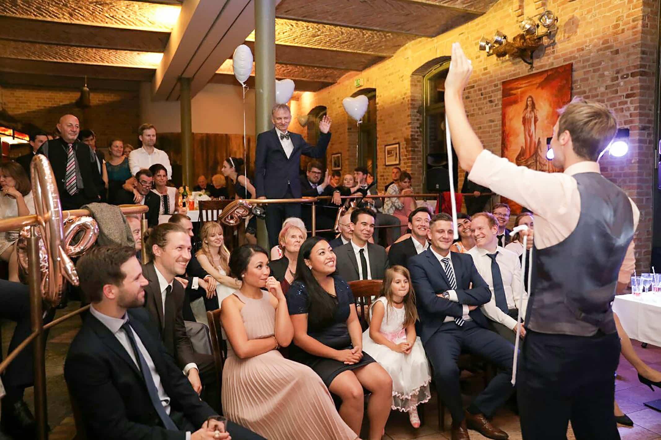 Auf einer Hochzeit bringt der Magier das Publikum mit seinen Zauberseilen zum Staunen. Sie sehen ihn ungläubig an und freuen sich.