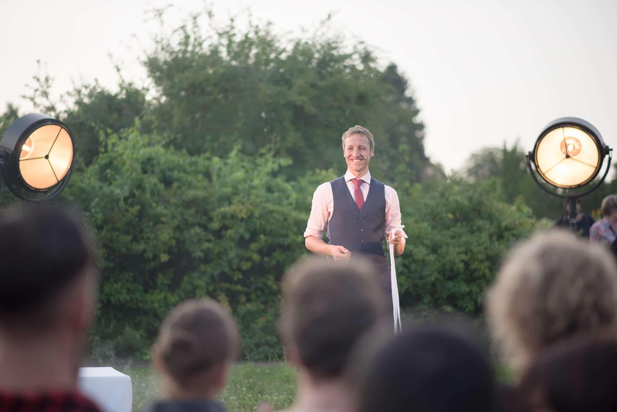 Bei einem Großevent im Botanischen Garten präsentiert der Zauberer Fabian Schneekind seine Bühnenshow. Man sieht ihn ins Publikum lächeln.
