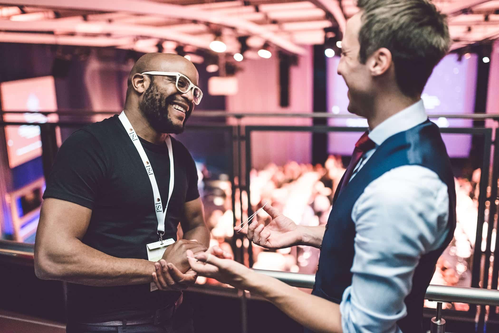 Fabian Schneekind unterhält einen Gast im VIP Bereich mit seiner Zauberei. Beide lachen dabei.