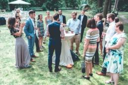 Diese Hochzeitsidee ist gelungen. Die Familien des Brautpaares rücken einander näher um gemeinsam den Zauberer zu sehen. Sie lachen und haben zusammen Spaß.