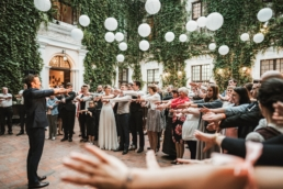 Auf einer Hochzeit präsentiert Fabian Schneekind seine Bühnenshow, bei der am Ende das Brautpaar mitmachen darf. Die Gäste stehen im Halbkreis um ihn herum und machen seine Beobachtungsaufgabe mit. Dazu strecken sie alle ihre Hände aus und machen mit ihnen das nach, was der Zauberer vormacht. Man sieht viele fröhliche Gesichter dabei.
