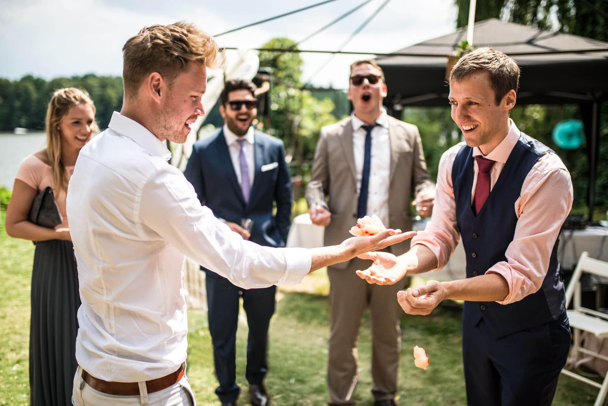 Der Zauberer zeigt den Hochzeitsgästen einen Zaubertrick in ihren eigenen Händen. Die Überraschung ist ihren Gesichtern anzusehen. Zwei von ihnen haben den Mund staunend weit aufgerissen.