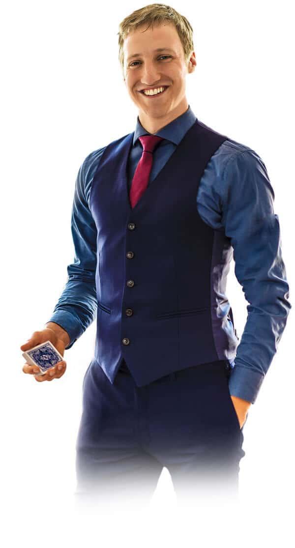 Der Zauberer in Potsdam hält in seiner rechten Hand Spielkarten und lächelt.